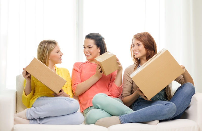 Women sitting on a couch holding different sized cardboard boxes, smiling at each other.